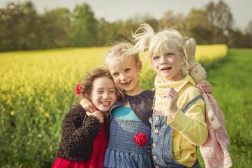 Drei kleine Mädchen vor Rapsfeld