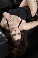 Junge Frau trägt schwarzen Badeanzug auf schwarzer Leder-Couch