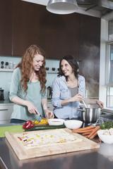 Portrait von zwei Freundinnen, die zusammen kochen