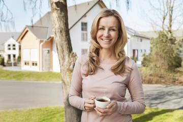 Lächelnde Frau mit Tasse Kaffee, vor Wohngebiet