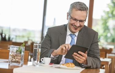 Geschäftsmann im Restaurant mit Tablet-PC