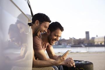 Zwei lachende Männer sitzen im Auto Blick auf Tablet-PC