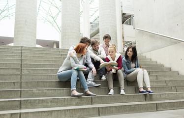 Gruppe von Studenten mit Bücher sitzt auf Treppen