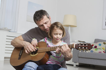 Vater lehrt Tochter Gitarre zu spielen