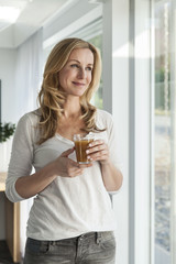 Frau glücklich mit Getränk, in ihrem hellen, modernen Haus