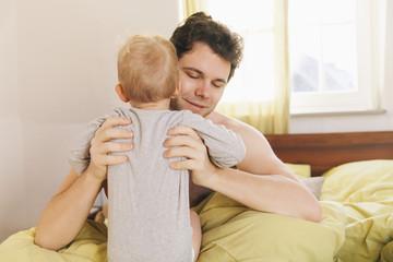 Vater sitzt im Bett, hebt Kleinkind