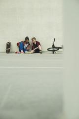 Zwei Jungen sitzen auf dem Boden mit Handy