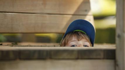 Kleiner Junge versteckt sich am Spielplatz