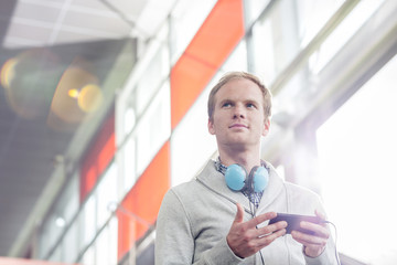 Junger Mann mit Handy und Kopfhörer
