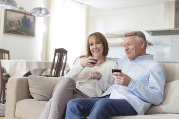 Älteres Ehepaar trinkt Rotwein zu Hause