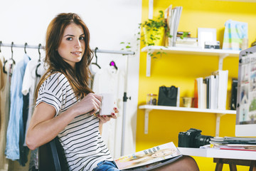 Weibliche Mode-Blogger mit Kaffeetasse in ihrem Büro