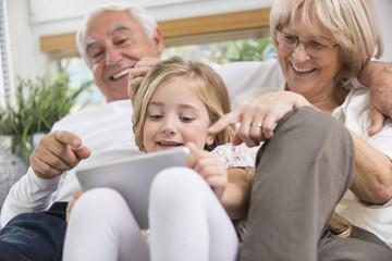 Paar und Enkelin sitzen mit Tablet-PC auf dem Sofa im Wohnzimmer