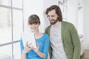 Blick auf Tablet-PC in einem kreativen Büro, zwei Kollegen