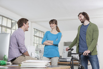 Drei Kollegen in einem Büro sprechen