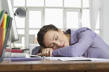 Frau zu Hause schlafend am Schreibtisch mit Computer