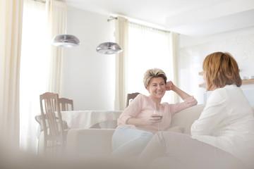 Zwei alte Freundinnen sitzen auf einer Couch im Wohnzimmer