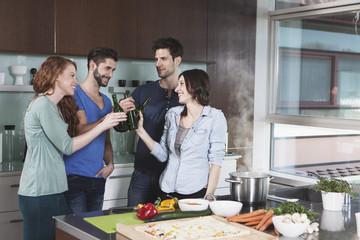 Vier Freunden Toasten mit Bierflaschen in einer Küche