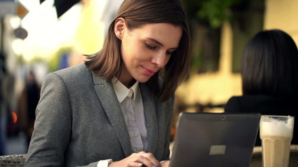 Young attractive businesswoman working on laptop, sitting in caf