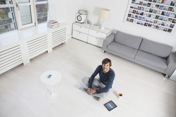Mann sitzt auf dem Boden im Wohnzimmer