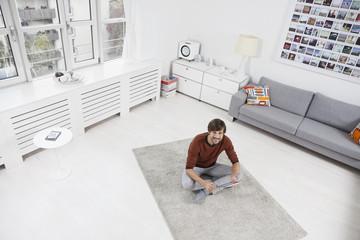Mann sitzt auf dem Boden, mit Tablet-PC
