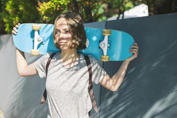 Junge Frau mit Skateboard auf ihren Schultern
