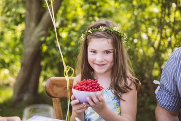 Mädchen hält Schale mit Johannisbeeren im Garten