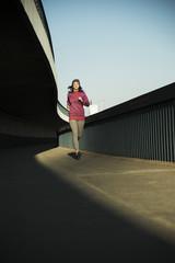 Joggerin unterwegs auf einer Brücke