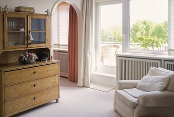 Wohnraum mit Sessel und altem Schrank