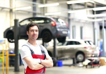 Zuversichtlicher Kfz-Mechaniker in einer Werkstatt