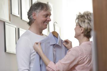 Ältere Frau hilft ihrem Mann Kleidung auszusuchen