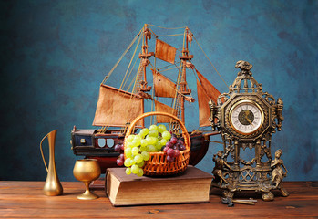 Fresh grapes in a wicker basket and a clock
