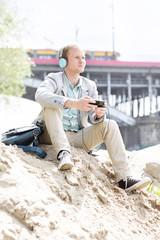 Polen, Warschau, junger Mann mit Kopfhörern am Flussufer