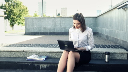 Young attractive businesswoman working on laptop while sitting o