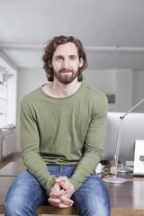 Mann sitzt auf einem Schreibtisch in einem Büro