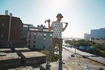 Junger Mann mit Golfschläger, Blick auf Stadt, cool