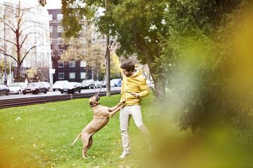 Junger Mann spielt mit seinem Hund auf Grünstreifen