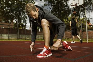 Junger Basketball-Spieler, Schnürsenkel binden