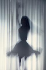 Silhouette einer jungen Frau, tanzend vor einem weißen Vorhang