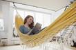 Lächelnde Frau entspannt mit Tablet-Computer in einer Hängematte in ihrer Wohnung