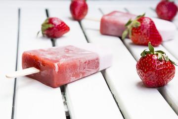 Zwei Erdbeer-Eis-Lollies und Erdbeeren auf weißem Holz