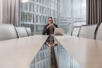 Geschäftsmann sitzt am Konferenztisch im Hotel