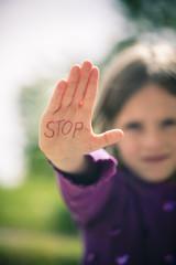 Kleines Mädchen, die Handfläche mit dem Wort STOP darauf