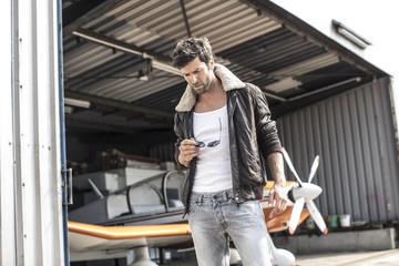 Mann mit Lederjacke steht vor Propellerflugzeug am Hangar