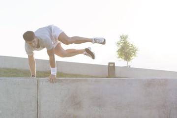 Polen, Warschau, Junger Mann springt über Mauer