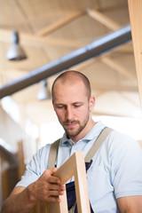 Zimmermann untersucht Stück Holz