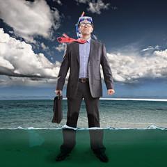 Geschäftsmann steht knöcheltief im Wasser, trägt Schnorchel