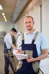 Handwerker in der Werkstatt macht Notizen