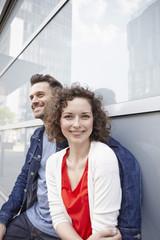 Deutschland, Nordrhein-Westfalen, Köln, Paar lehnt an der Fassade im Rheinauhafen