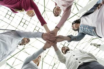 Gruppe von jungen Menschen stapeln ihre Hände