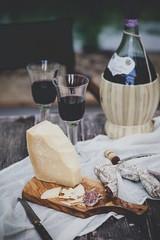 Italienischer Käse Grana Padano, Salami, zwei Gläser und eine Flasche Chianti